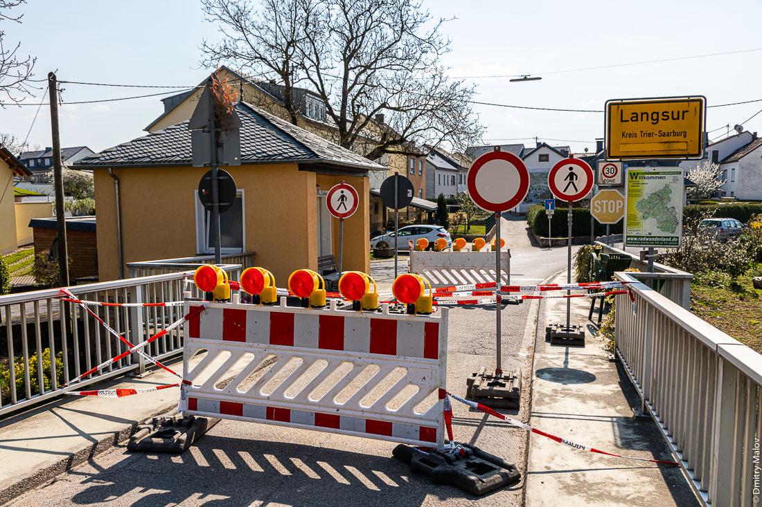 Пограничный мост через реку Зауэр около люксембуржского Васербилига в немецкий Лангсур перекрыт дорожными блоками и полицейскими лентами из-за пандемии коронавируса. Граница закрыта. Border bridge over Sûre river near Wasserbillig, Luxembourg to Langsur, Germany is closed due to COVID-19 pandemics.