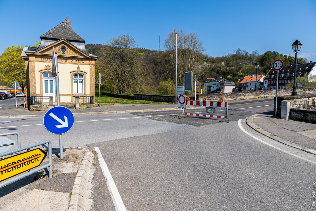 Historical Customs office (Douanes Zoll) at the border of Luxembourg and Germany in Echternach. Road sign with the direction to German Echternacherbruck is crossed out due to road closure because of Covid-19 pandemics