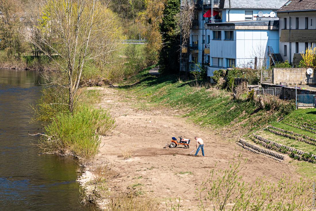 Мужчина обрабатывает поле на мини-тракторе на берегу реки Зауэр, Эхтернахербрюк, Германия. A man cultivates a field with a mini-tractor on a bank of Sauer river, Echternaherbruck, Germany.