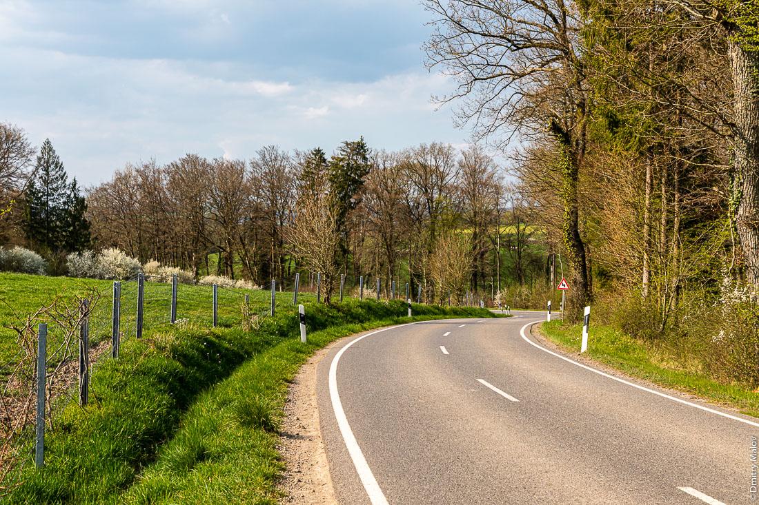 Road and barbed wire fence at Luxembourg-Belgium border at the west of Luxembourg. Дорога и забор из колючей проволоки на люксембуржско-бельгийскогой границе на западе Люксембурга