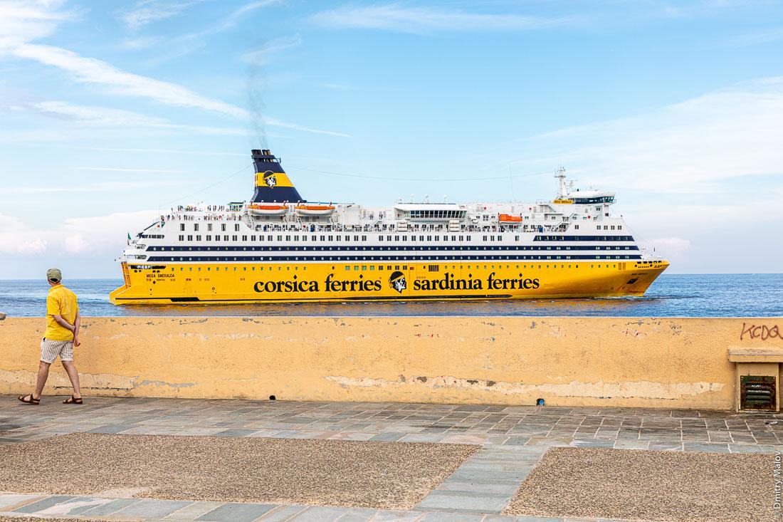 Мужчина в жёлтом прогуливается по набережной Бастии, Корсика. Отправление парома Corsica-Sardinia ferries