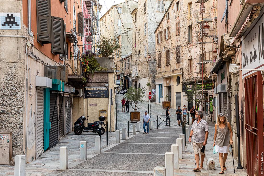 Пожилая пара, мужчина и женщина в возрасте с белым пёсиком типа болонки на улицах Бастии, Корсика