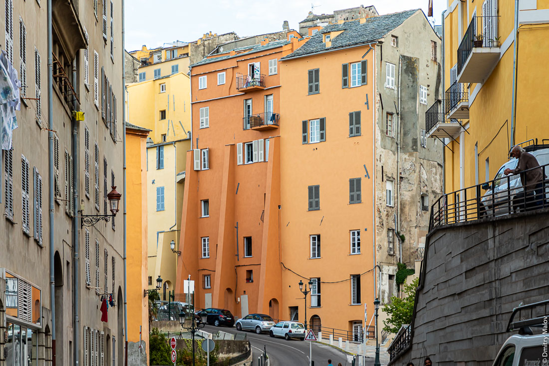Контрфорсы у домов на улице в Бастии, Корсика. Пожилой мужчина-француз-дед грустно смотрит на улицу