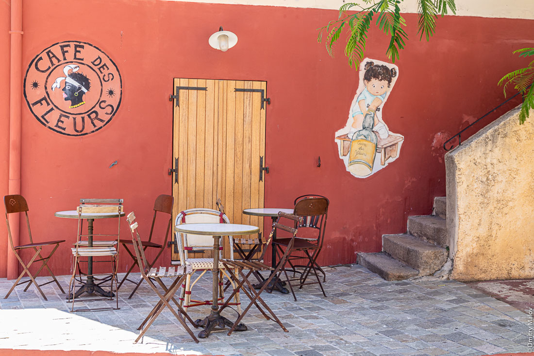 Cafe des Fleurs logo resembling Moor's head as on the flag of Corsica, with red wall background. Calvi