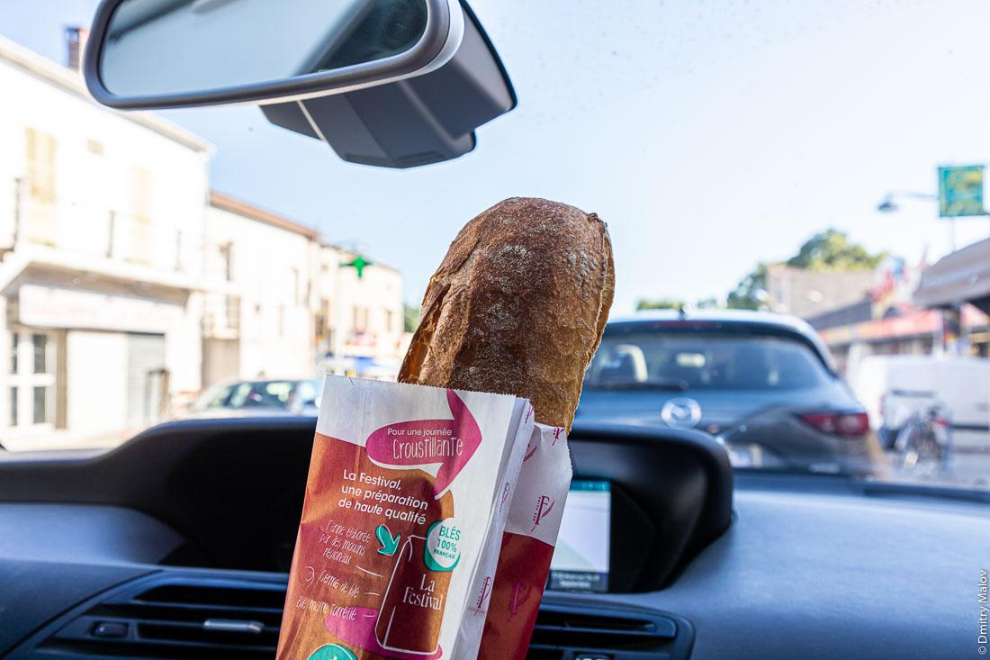 Пассажир на переднем сидении в машине демонстирует багет, Корсика, Франция