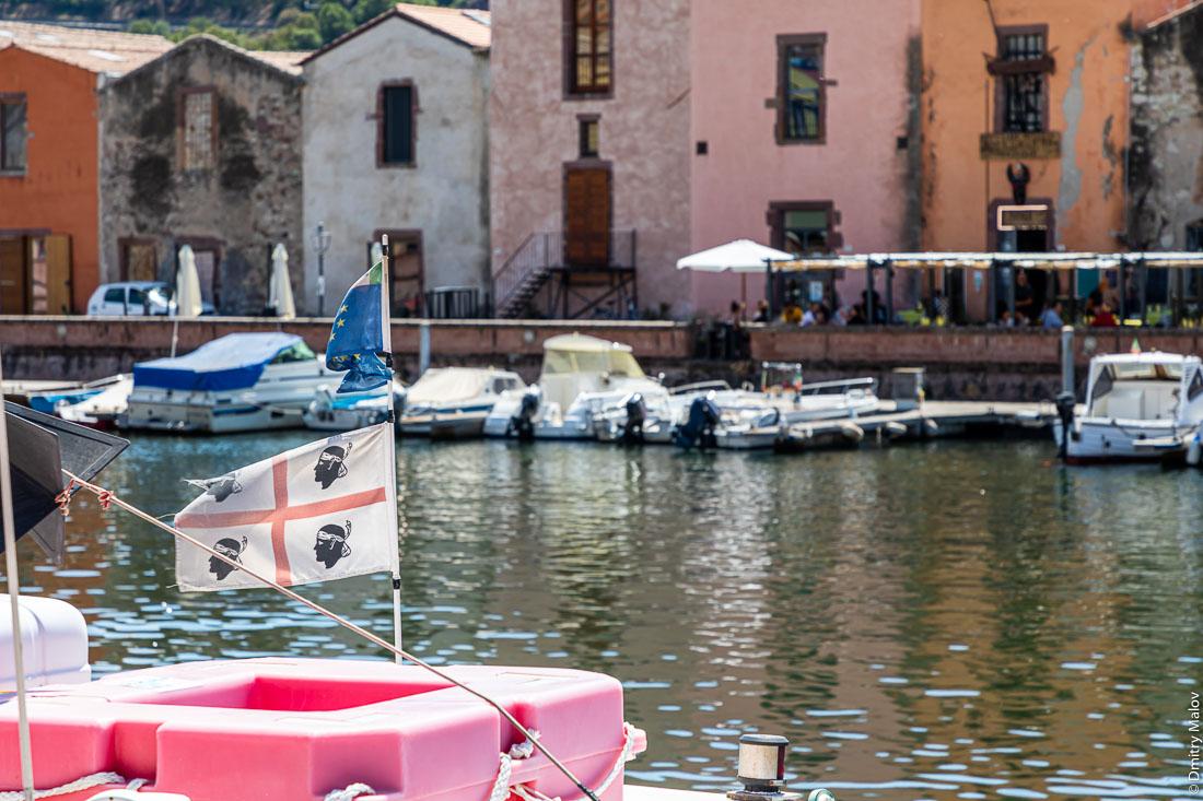 Флаг Сардинии на фоне набережной реки с пришвартованными моторками в городе Боза