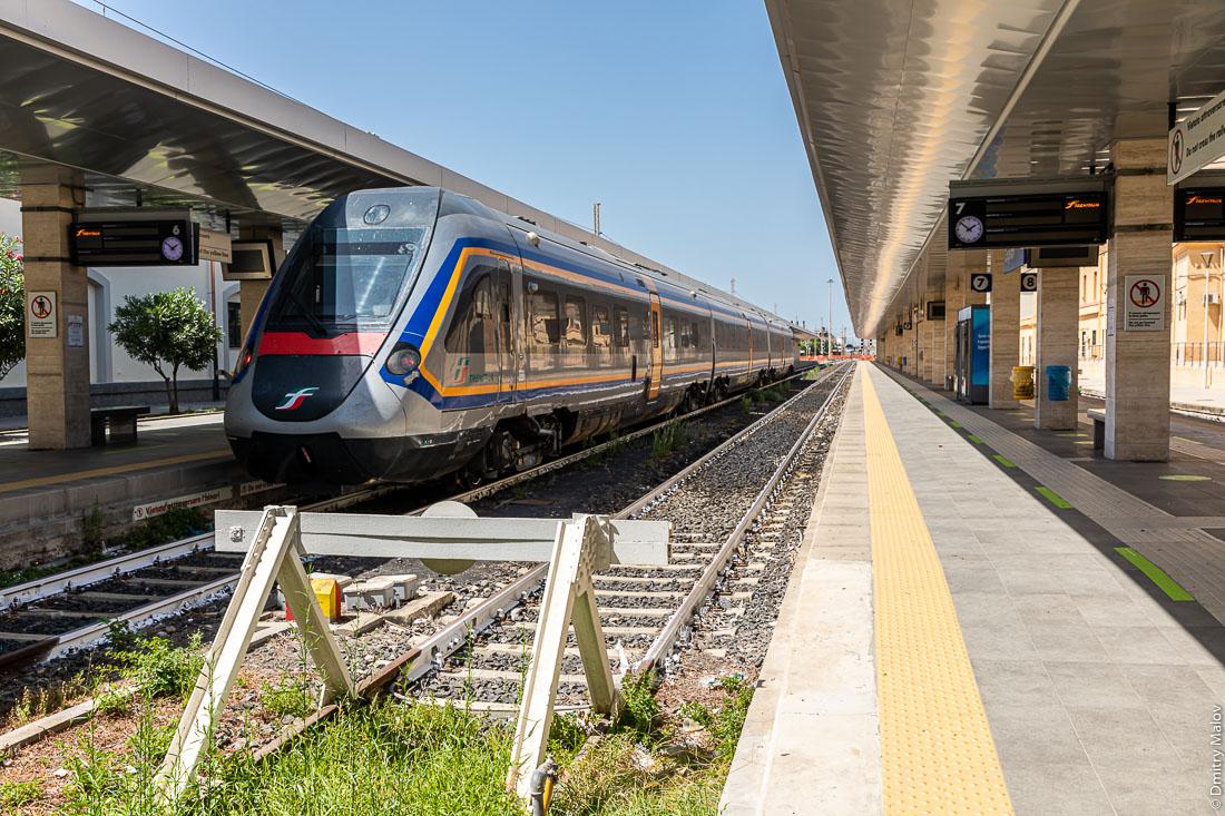 Скоростной поезд у пустой платформы центрального воказала. Кальяри, Сардиния, Италия. Рельсы покрашены белой краской
