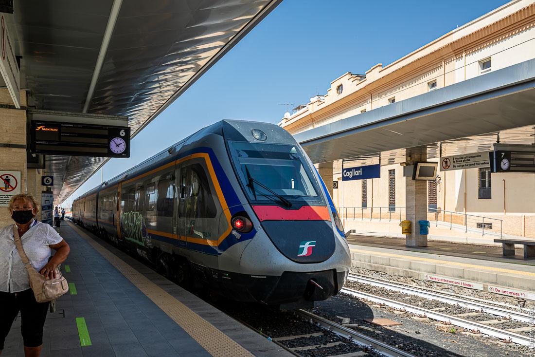 Скоростной поезд у платформы центрального вокзала, люди ждут поезд. Кальяри, Сардиния, Италия. Рельсы покрашены белой краской