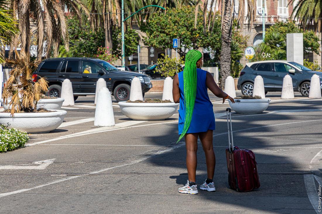 Девушка-туристска с зелёным волосами и чемоданом, Кальяри, Сардиния, Италия.