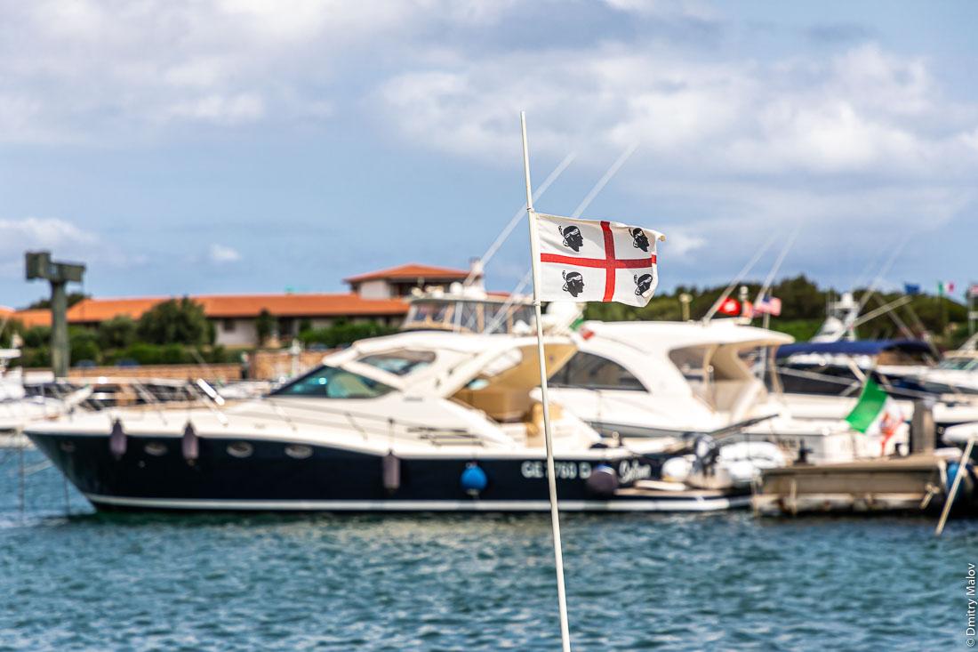 Флаг Сардинии на фоне марины с яхтами и катерами