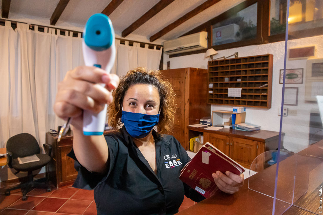 Receptionist lady in hotel in a face mask takes a measurement with a thermometer, Sardinia
