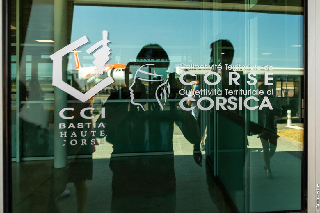 Corsica's Moor's head symbol - tourism logo on airport entrance, Bastia. Collectivité territoriale de Corse. CCI Bastia Haute Corse.