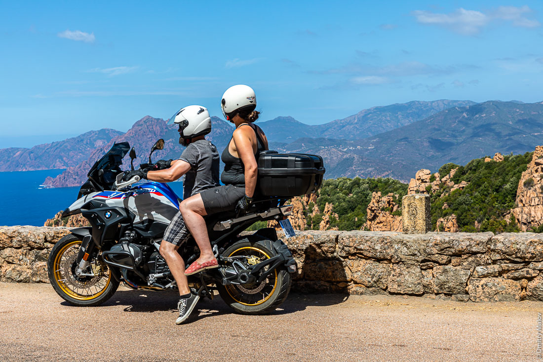 Middle age couple on a motorbike. Beatuful roadside scenery, sea, mountains, Corsica