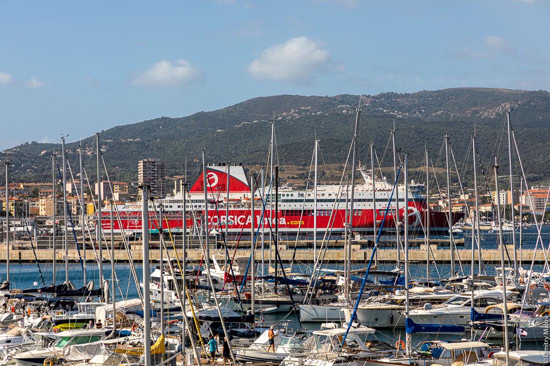 Красный паром Corsica Linea c логотипом в виде корсиканского символа головы мавра выглядывает из-за мачт яхт в порту Аяччо, Корсика.