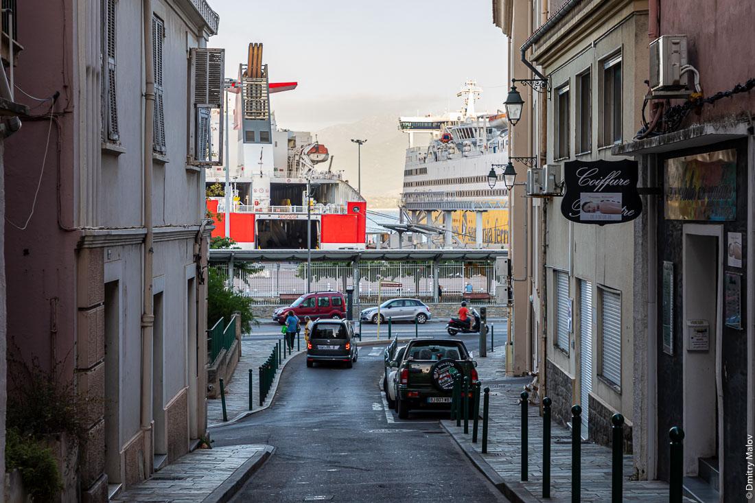 City street with ferries on the background. Ajaccio, Corsica. Паромы выглядывают из-за домов. Аяччо, Корсика.