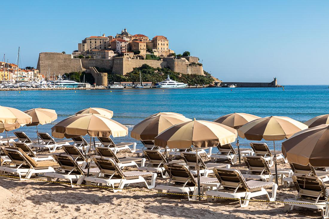 Calvi, Corisca. Зонтики на пляже и цитадель Кальви, Корсика