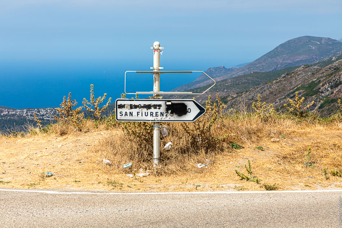 Road sign in Corsica with the French placenames blotted out by nationalists. Корсика. Французские названия на дорожных знаках зачеркнуты