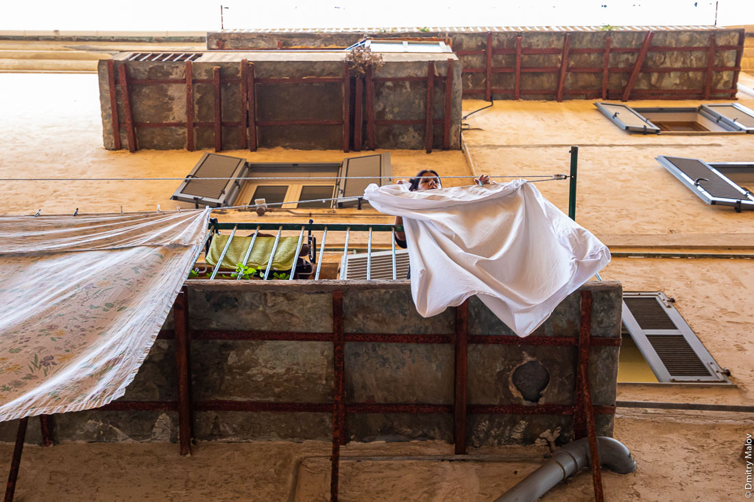 Хозяйка развешивает бельё на балконе, Бестия, Корсика