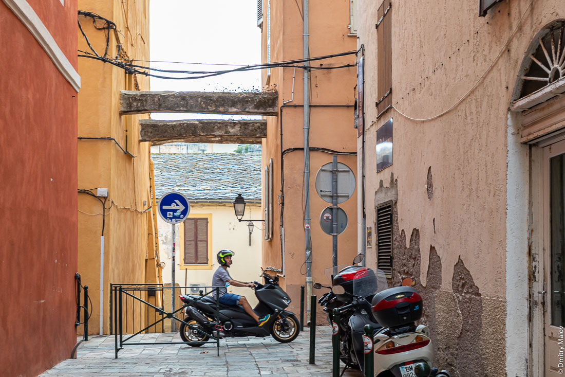 Распоры между домами на узкой улице, Бестия, Корсика. Мужчина-француз на мотороллере
