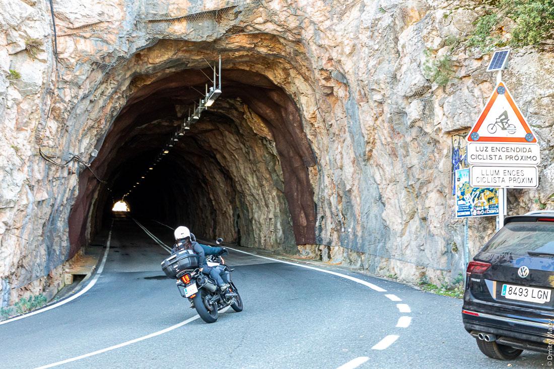 В старый тоннель без обделки в горах въезжает мотоциклист с девушкой. Мальорка, Испания