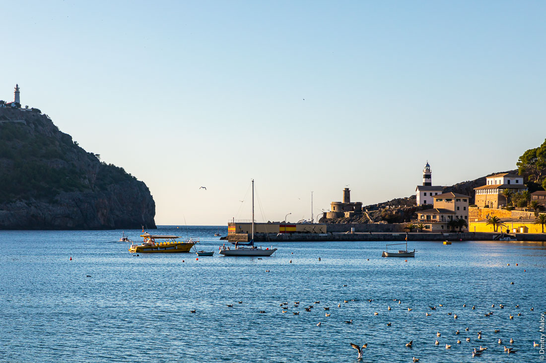 Зактное солнце, бухта, 2 маяка, лодки и стая уток. Порт-де-Сольер. Мальорка, Испания.