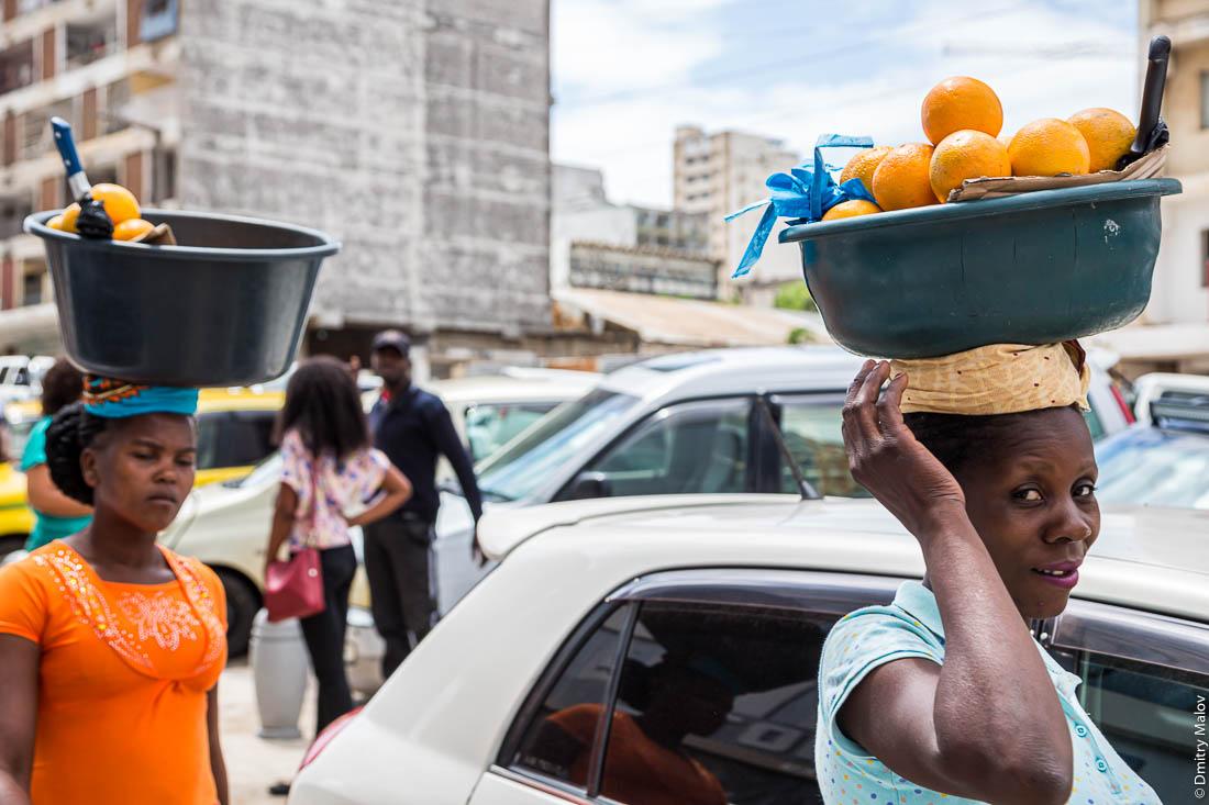 Негритянки несут тазы с апельсинами на голове. Город Мапуто, Мозамбик, Африка