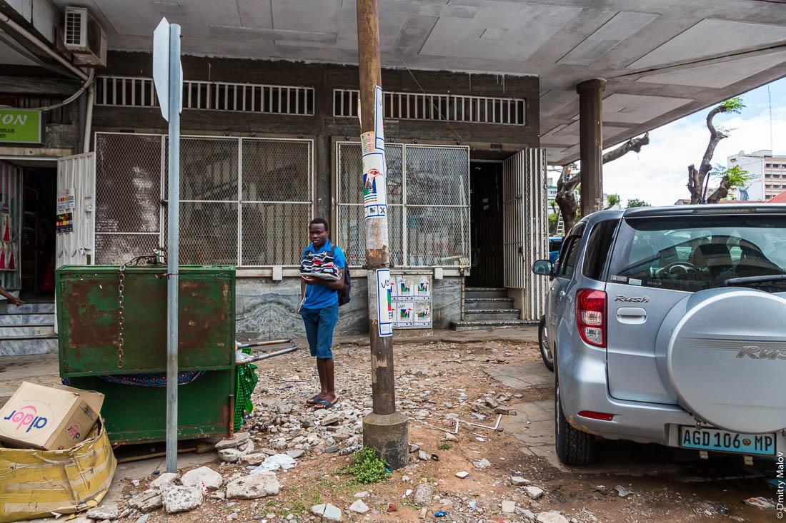 Подросток торгует носками с рук на улице. Город Мапуту, Мозамбик, Африка