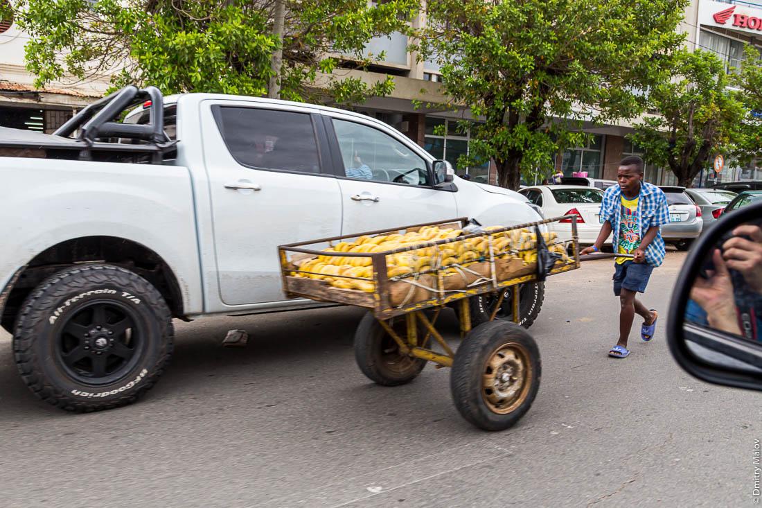 Африканец толкает телегу с банами против напряжённого автотрафика. Город Мапуто, Мозамбик, Африка