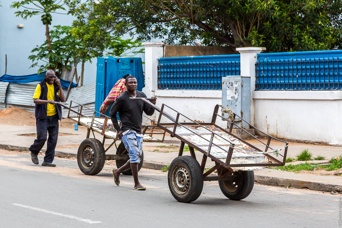 Африканцы толкают пустые телеги по улицам города Мапуто, Мозамбик, Африка