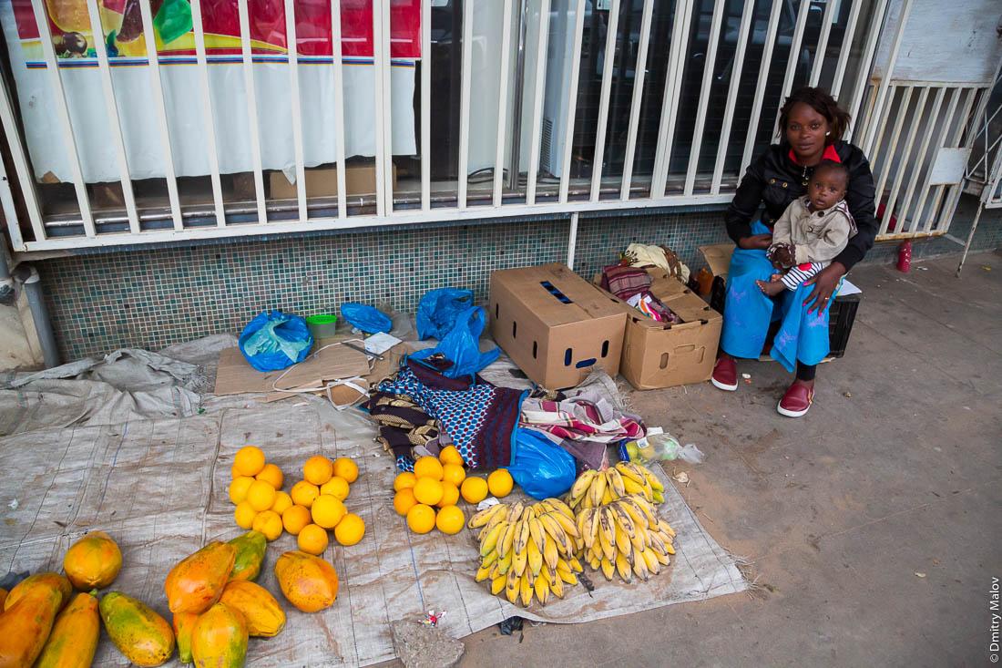 Чёрная женщина с ребёнком на руках торгует с земли папаями, апельсинами, бананами. Мапуто, Мозамбик