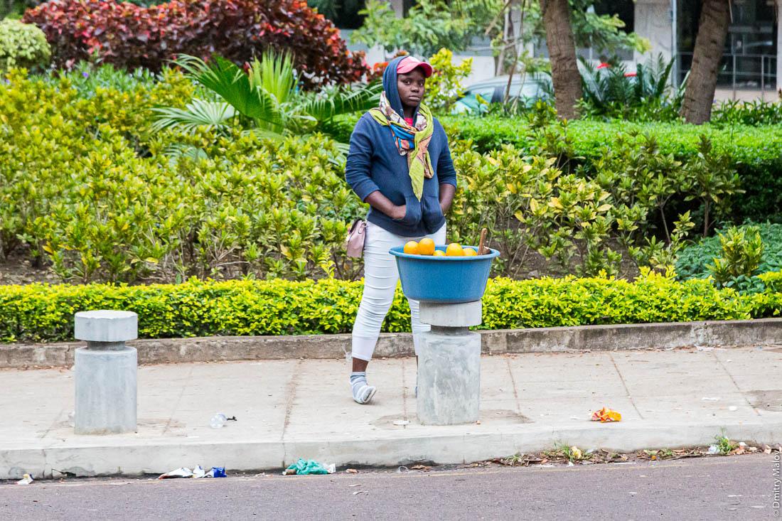 Чёрная женщина торгует с рук из таза апельсинами. Мапуто, Мозамбик