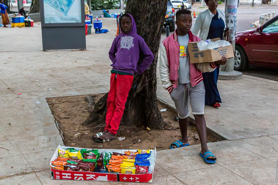 Подростки продают чипсы Lays, Simba, Doritos с рук на улице. Уличная торговля. Город Мапуту, Мозамбик, Африка