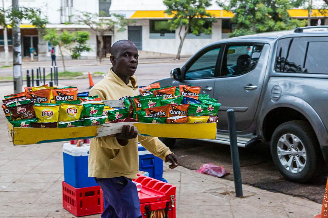 Житель Мапуто продаёт чипсы Lays, Simba, Doritos с рук на улице. Уличная торговля. Мозамбик