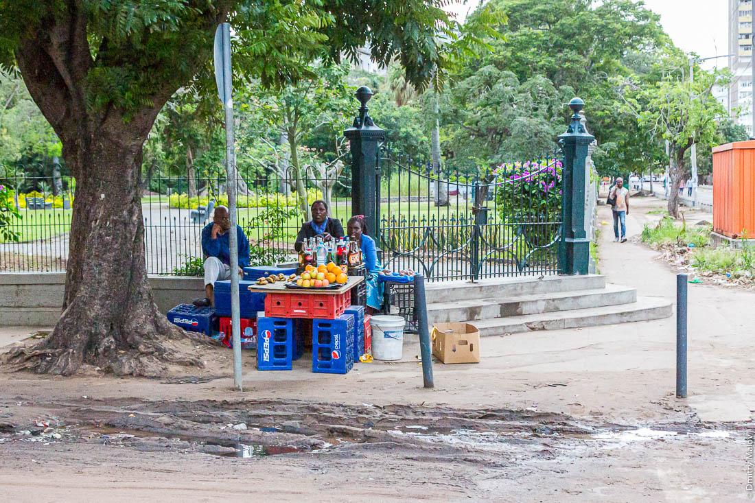 Уличная торговля апельсинами с ящиков Pepsi у ограды колониального парка, Мапуто, Мозамбик