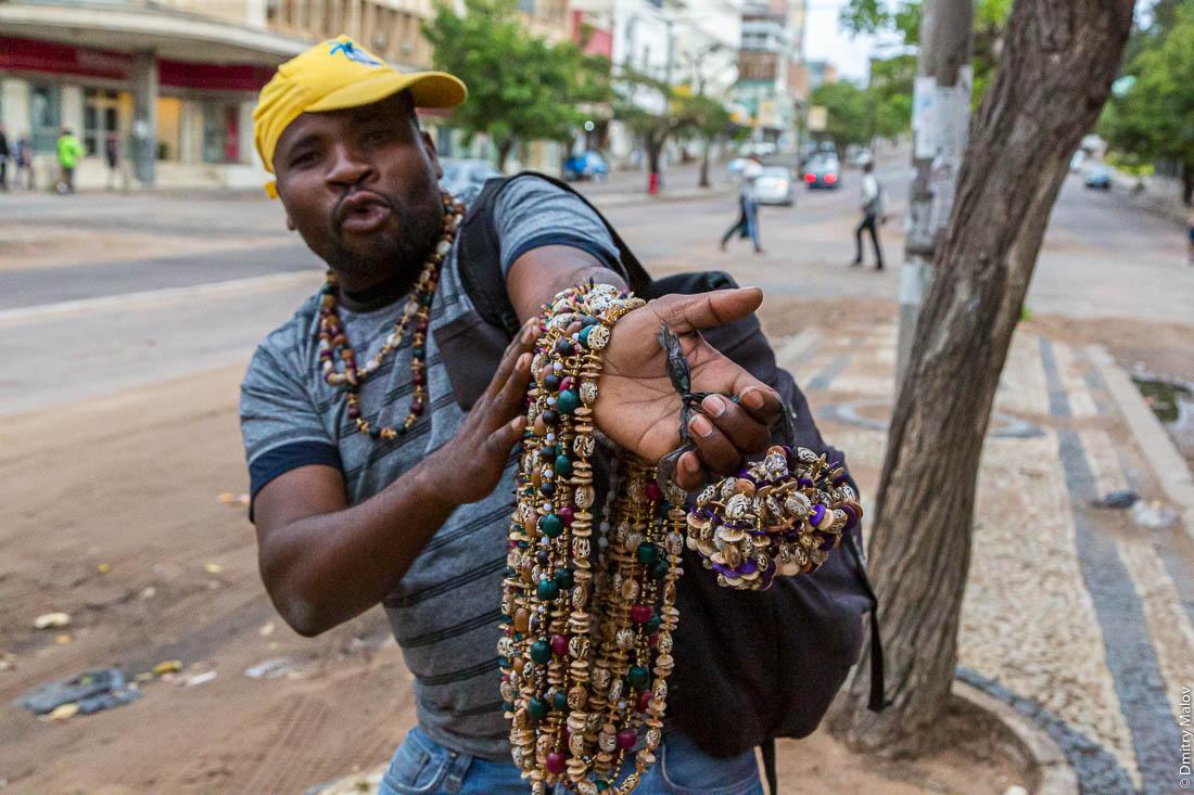 Житель Мапуто продаёт бусы с рук на улице. Уличная торговля. Мозамбик