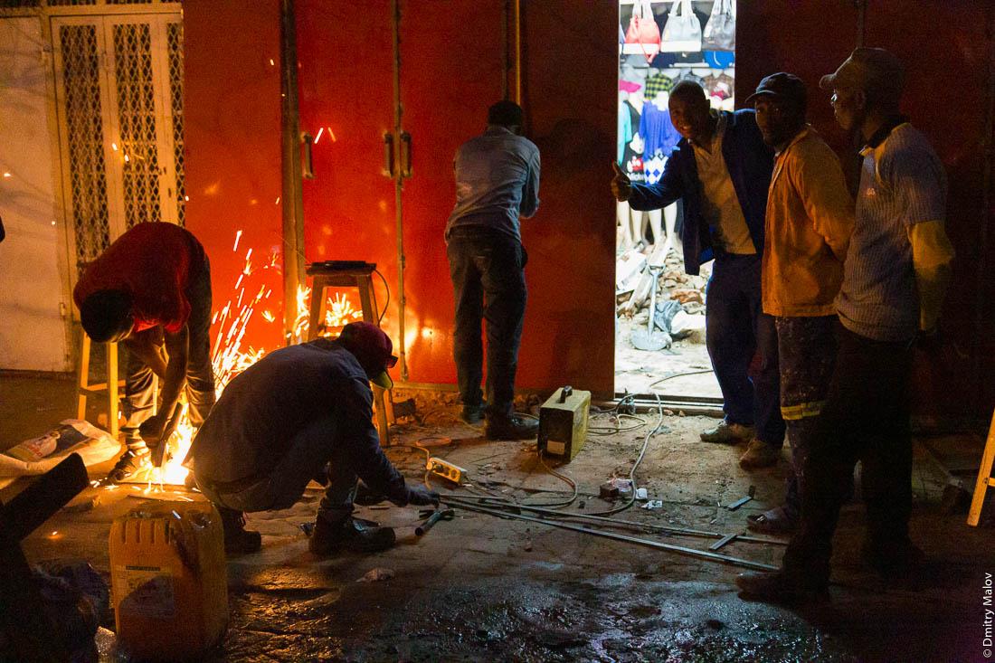 Ночная жизнь на улицах Мапуту, Мозамбик, Африка. Рабочие с болгаркой и сваркой