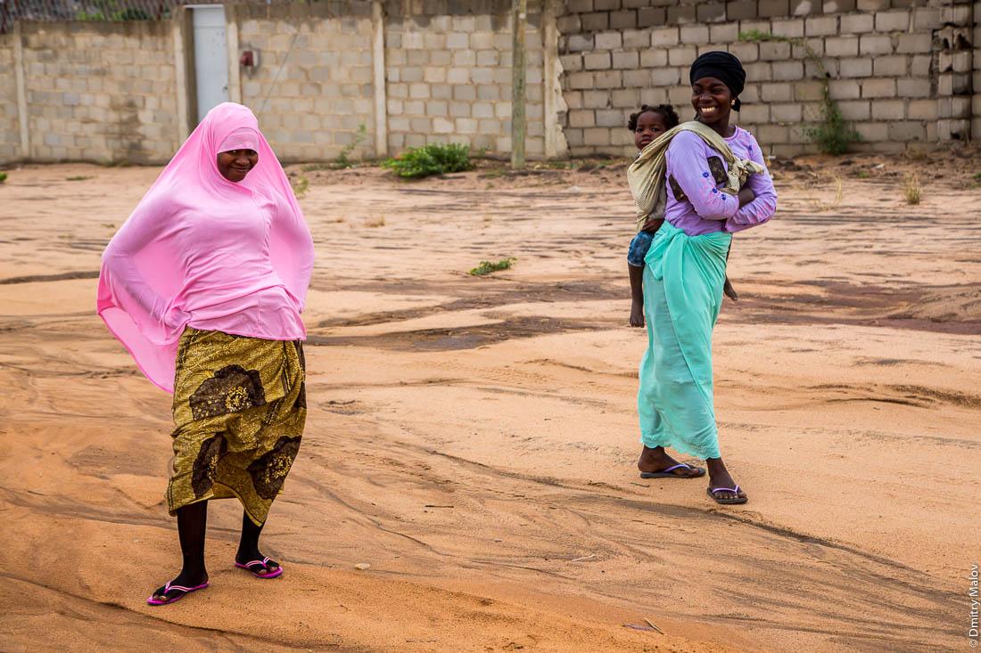 Красочно цветасто одетые чёрные женщины-мусульманки в розовом и чёрном платках и цветных юбках. Нампула, Мозамбик, Африка