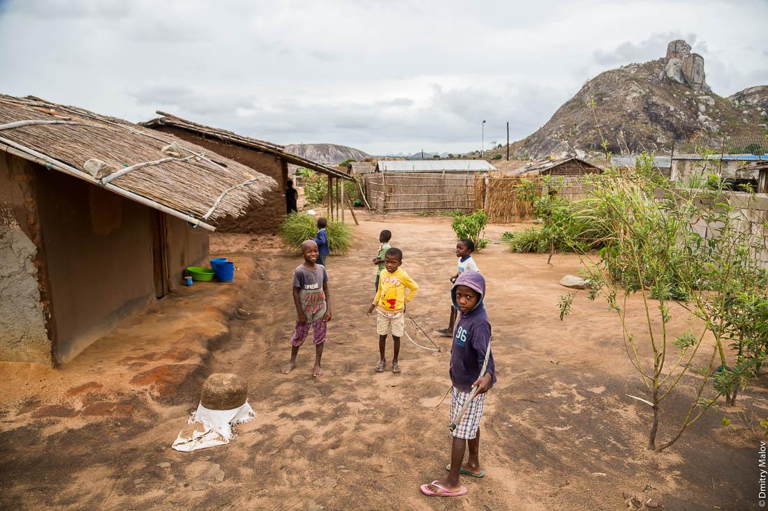 Чёрные дети, чёрные мальчики в деревне макуа, негритята, дети народа макуа (вамакуа, маква, макоане, нгуру) на фоне скал-останцев и домов деревни. Дорога Нампула - остров Мозамбик, Мозамбик, Африка