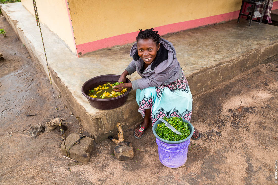 Африканка, чёрная женщина народа макуа моет овощи на пороге дома. Дорога Нампула - остров Мозамбик, Мозамбик, Африка