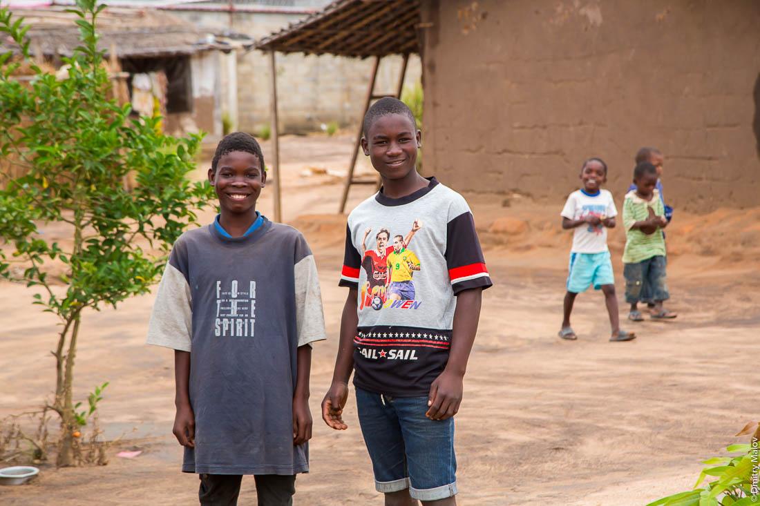 Чёрный подростки, африканские подростки, чёрные парни народа макуа (вамакуа, маква, макоане, нгуру) на фоне домов деревни. Дорога Нампула - остров Мозамбик, Мозамбик, Африка