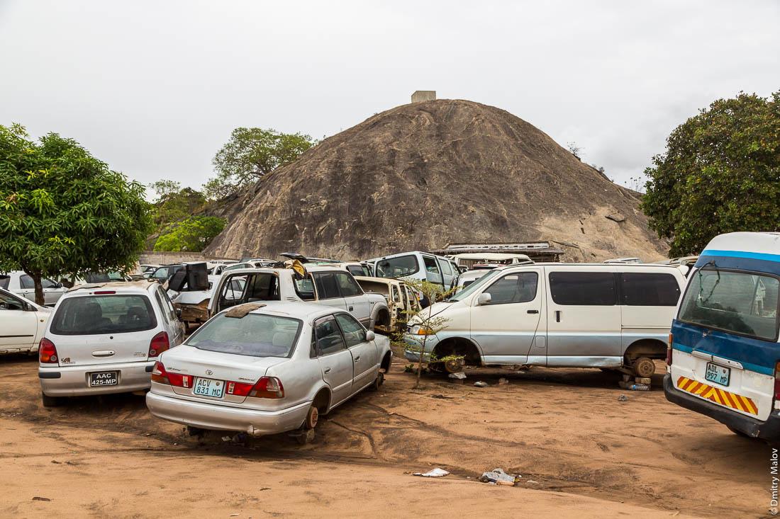 Автосвалка, автомобильная разборка, на фоне скалы-останца. Дорога Нампула - остров Мозамбик, Мозамбик, Африка