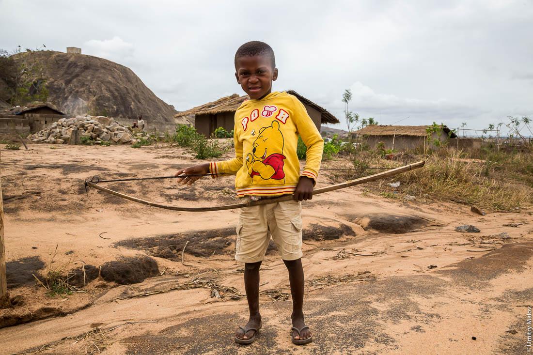 Чёрный мальчик с луком в деревне макуа, негритёнок, ребёнок народа макуа (вамакуа, маква, макоане, нгуру) на фоне скал-останцев и домов деревни. Дорога Нампула - остров Мозамбик, Мозамбик, Африка