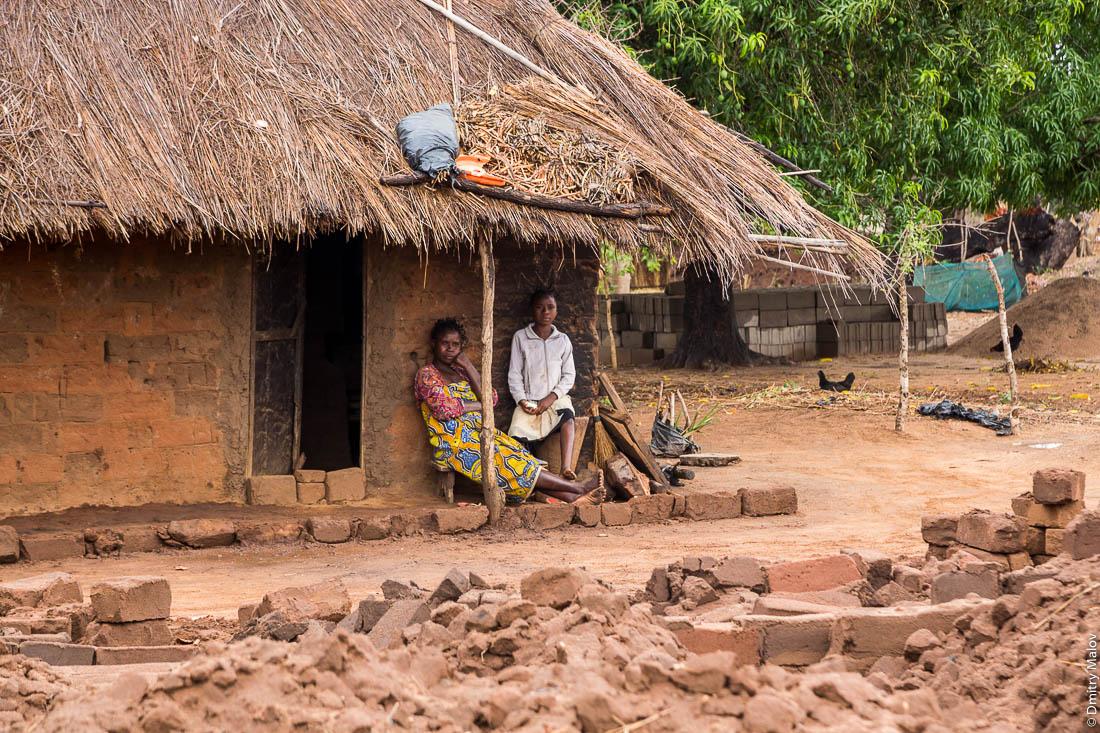 Две грустные чёрные женщины-африканки на крыльце дома из необожженного кирпича. Нампула, Мозамбик, Африка