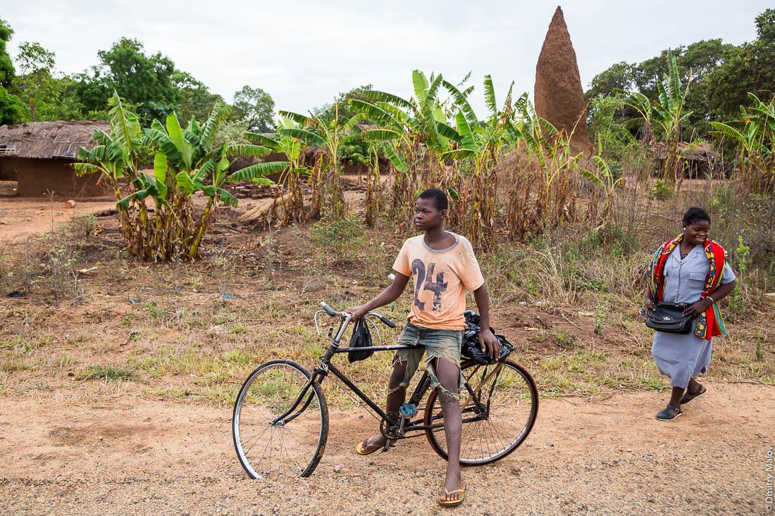 Черный подросток на велосипеде и красочно одетая в цветастое платье африканка, женщина на фоне гигантского термитника. Нампула, Мозамбик, Африка