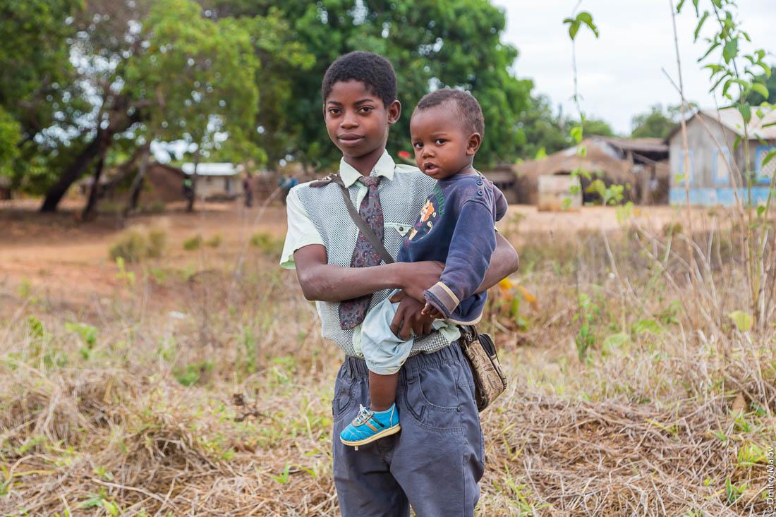 Чёрный мальчик-подросток держит маленького брата на руках. Нампула, Мозамбик, Африка