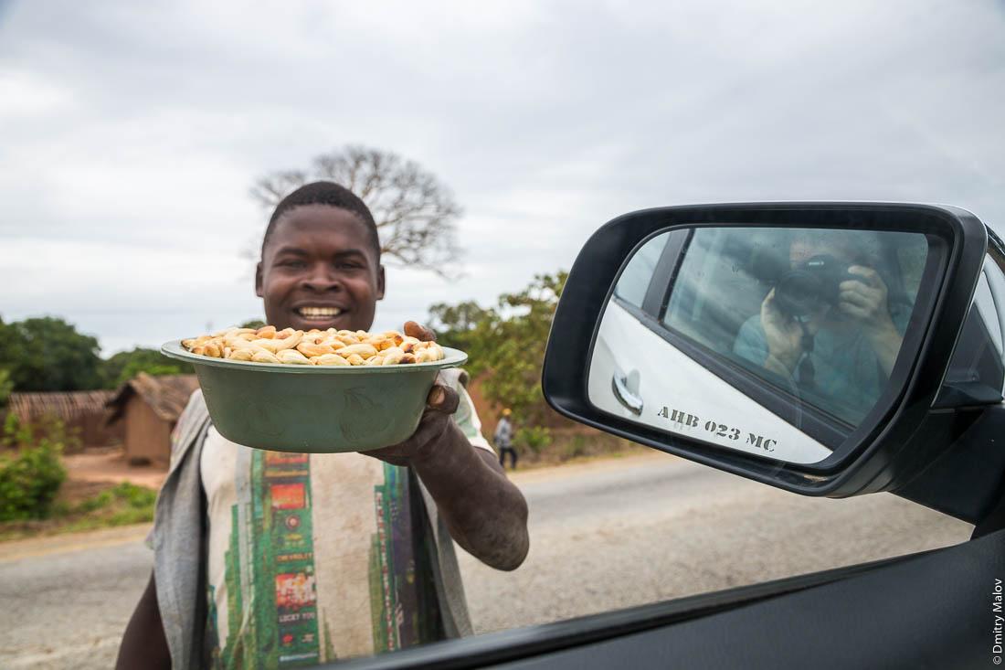 Черный парень, африканец продаёт кешью. Дорога Нампула - остров Мозамбик, Мозамбик, Африка
