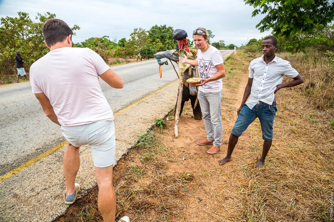 Миша Серяков и Денис Карепин снимают видеоблог на фоне чучула и уличного торговца. Дорога Нампула - остров Мозамбик, Мозамбик, Африка