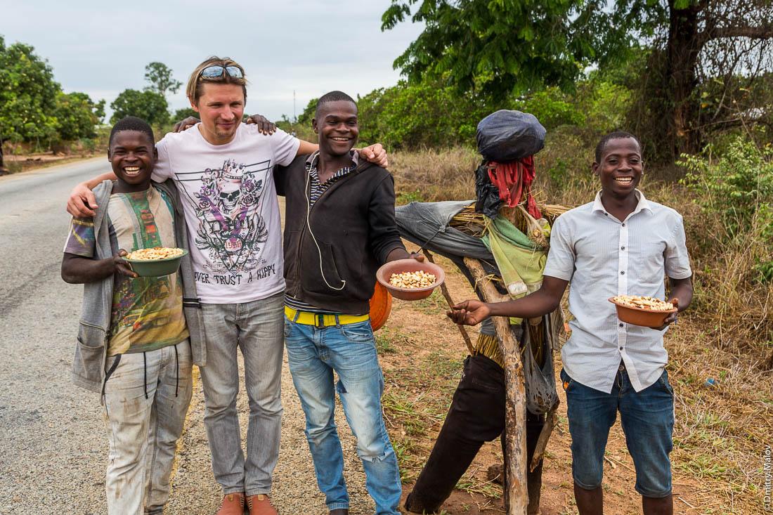 Михаил Серяков позирует с чёрными парнями, африканскими уличными торговцами кешью и их чучелом. Дорога Нампула - остров Мозамбик, Мозамбик, Африка