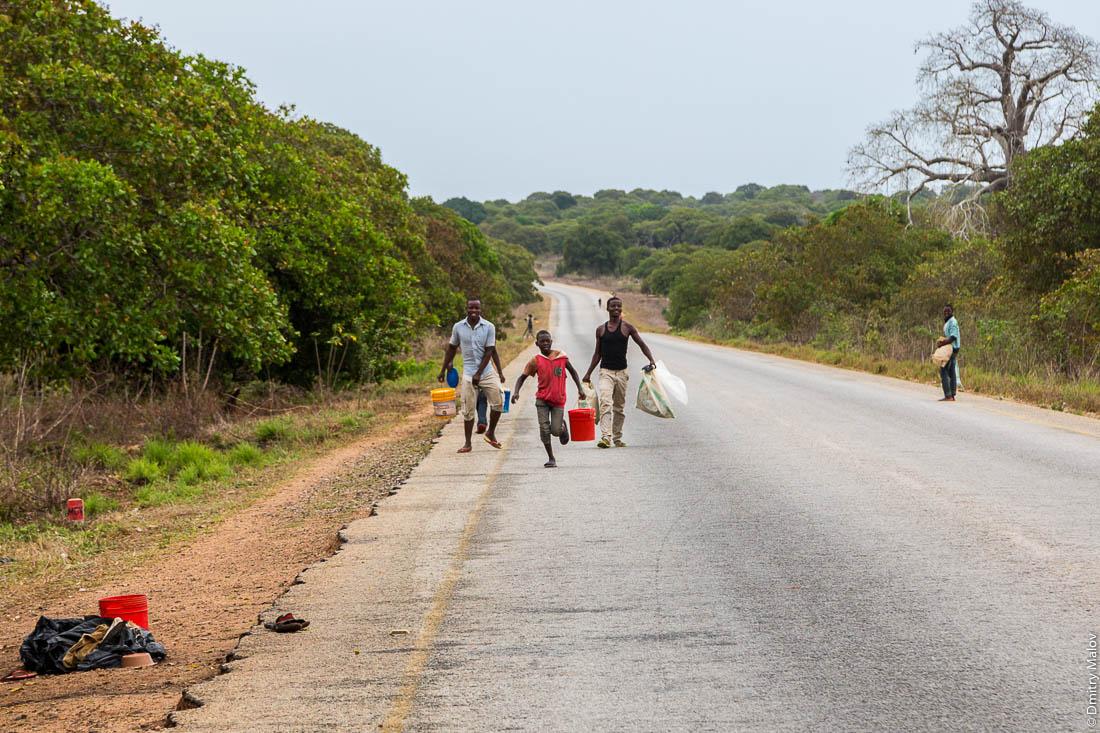 Придорожные торговцы бегут за машиной с туристами. Дорога Нампула - остров Мозамбик, Мозамбик, Африка