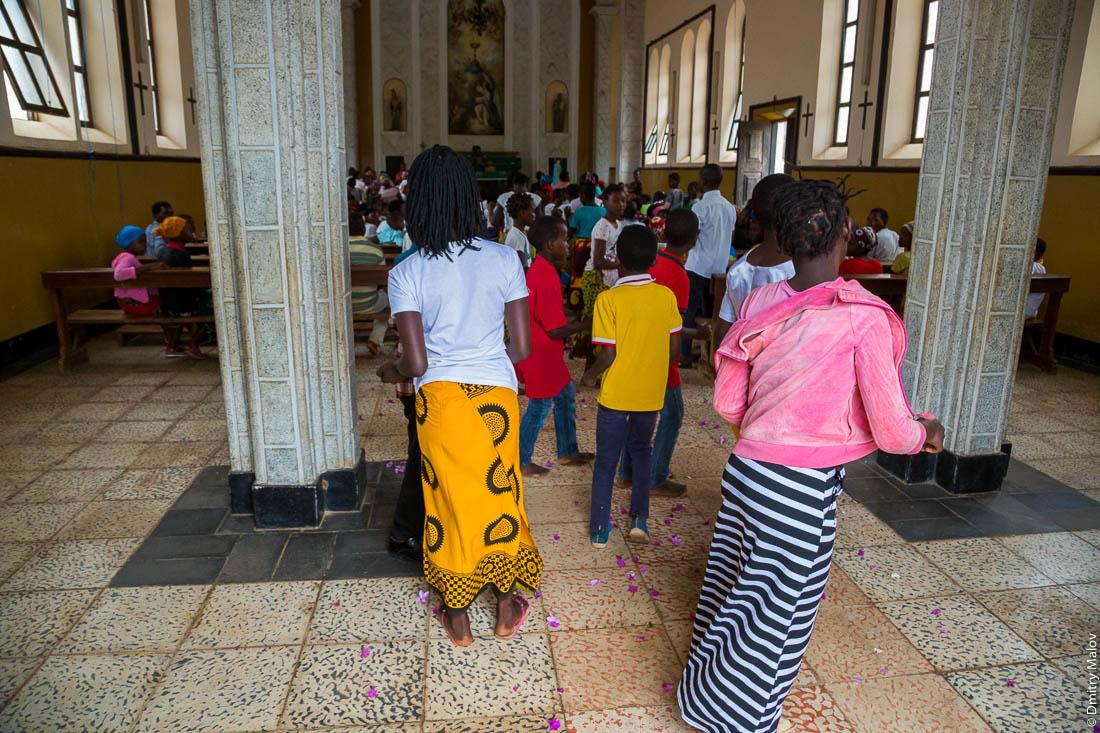 Воскресная месса, процессия. Чёрные девушки в жёлтых юбках танцуют в католическом храме, Santuário de S. M. Mãe do Redentor, Meconta, Mozambique.